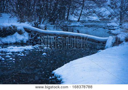 Unfrozen river during heavy snow at blue hour, mountain Kozomor, Serbia