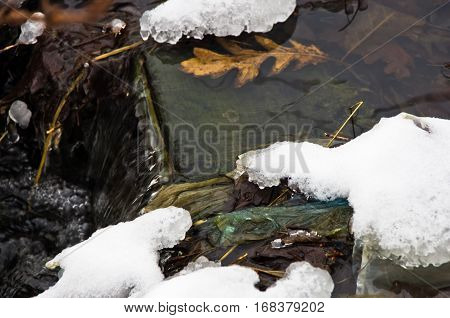 Small cascade of unfrozen water stream surrounded by snow in winter at mountain Kozomor, Serbia