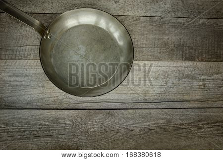 Vintage metalic skillet on the old wooden background. Top view.