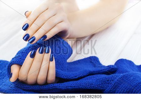 blue manicure with a blue knitted scarf on the white wooden table.