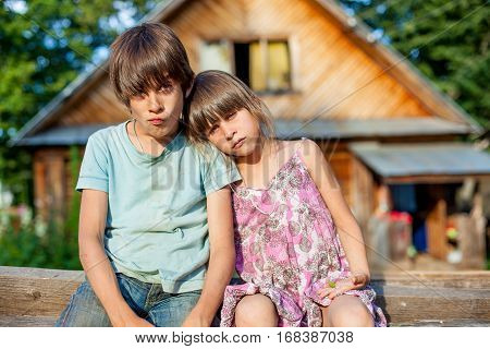 brother and sister sitting on a bench in the village shaggy unkempt