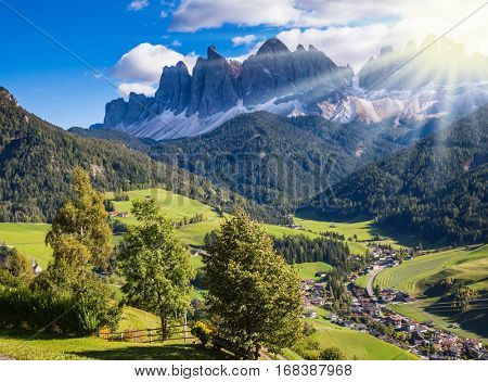 The concept of eco-tourism in Alpine meadows. Beautiful autumn day. The sun illuminates rural farm and green alpine valley in the Dolomites