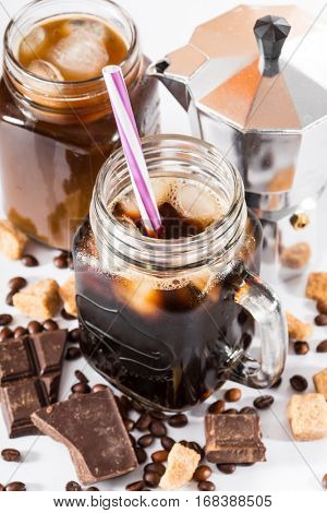 iced coffee in a large mug. coffee beans, pieces of chocolate and coffee pot on a white background