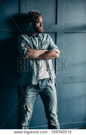 Irresistible man. Confident young bearded man in blue jeans shirt looking away and keeping arms crossed while standing against wall