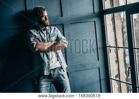 Thinking about... Handsome young bearded man in light jeans shirt keeping arms crossed and looking away while standing near the window