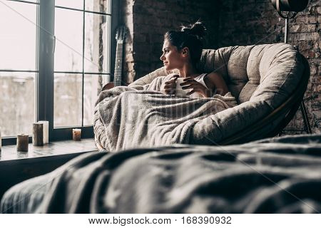 Beauty at home. Attractive young woman covered with blanket looking through window and holding a cup while sitting in an armchair at home