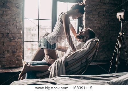 No rules for them. Young passionate couple looking on each other while spending free time at home