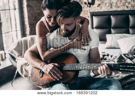 Playing by heart. Handsome young bearded man sitting in bed and playing guitar while attractive woman embracing him