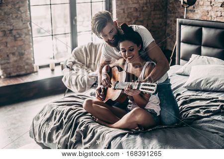 You are playing great! Handsome young bearded man teaching his girlfriend to play guitar while both sitting in bed at home together