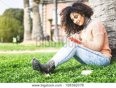 Happy young woman with curly hair writing her thoughts in her diary relaxing in the nature - A student girl aspiring journalist writing her ideas on her copybook outside university poster