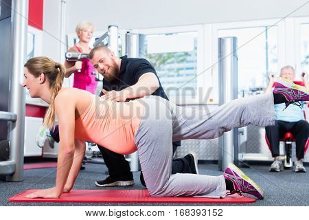 Pregnant woman working out with personal trainer at the gym