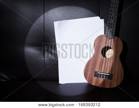 Ukulele in Sport Light and Blank Music Paper Notes.