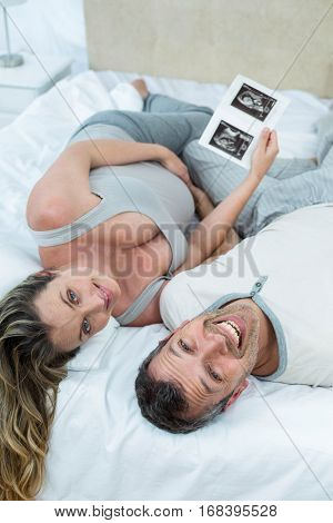 Expecting couple lying on bed and looking sonography reports