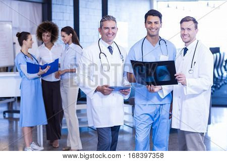 Portrait of doctors holding an x-ray and smiling in hospital