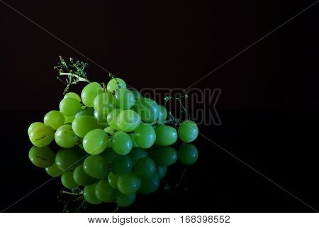 Green grapes on a reflective black surface.
