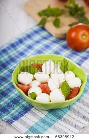 Mozzarella In A Green Plate On A Wooden Table. Mozzarella Balls With Basil Leaves And Tomato On A Wo