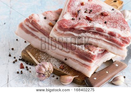 Fresh raw pork lard with spices for pickling on a cutting wooden board.
