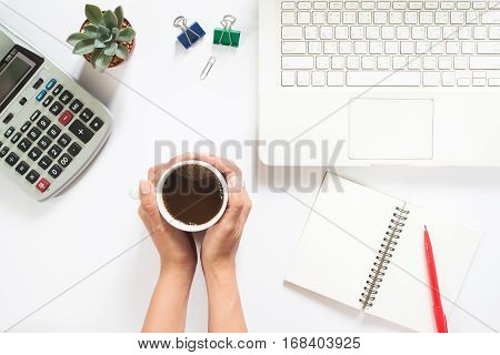 Overhead view of woman hand holding cup of coffee with laptop and calculator on white background Work space and accouting concept