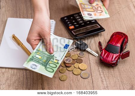 Car toy and key with calculator and euro money on desk