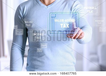 Man pushing VALUE-ADDED TAX button on virtual screen. Taxation concept