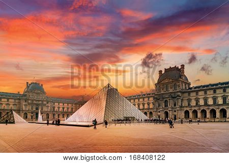 PARIS, FRANCE - DECEMBER 9, 2016: View of famous Louvre Museum with Louvre Pyramid at evening. Louvre Museum is one of the largest and most visited museums worldwide
