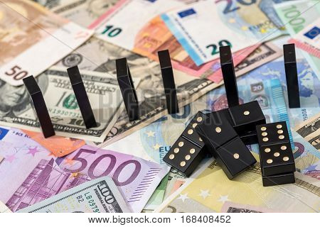 euro money and dominoes on top banknotes.