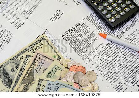 tax form w-4 dollar coin pen close up