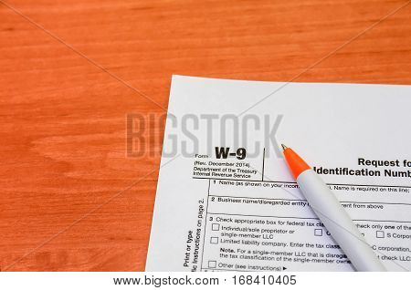 Income Taxes. w-9 and pen close up