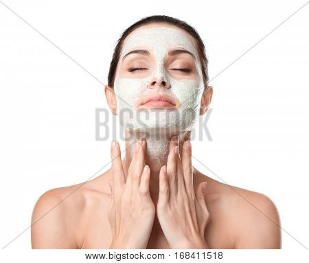 Beautiful young woman applying scrub mask on face, closeup
