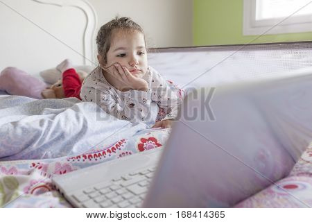 Little girl lying in bed and watching cartoons with a laptop in his bedroom. She looks entertained