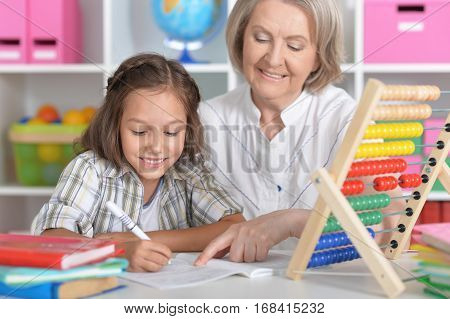 Portrait of a granny with her granddaughter doing homework