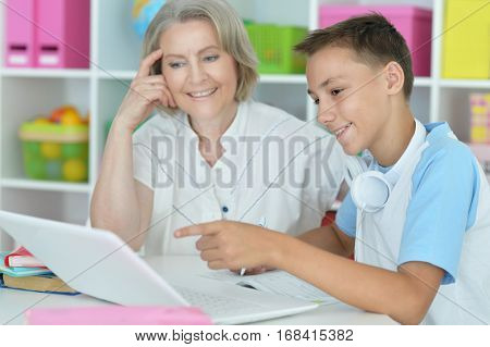 Portrait of a granny with her grandson using laptop