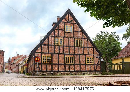 Gable of a medieval half-timbered old house in the Swedish town Lund, against blue sky.