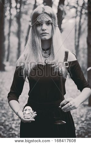 Young witch with pink hair performing a magical ritual with a black dark candle black and white photo faded colors selected focus