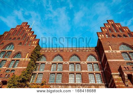 Lund, Sweden, November 8, 2016: Lund University Library. An huge brick facade with ivy against blue sky, Established in 1666. Since 1698 it has received legal deposit copies of everything printed in the country.