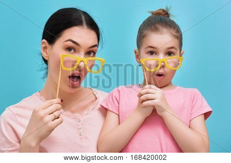 Funny family on a background of bright blue wall. Mother and her daughter girl with a paper accessories. Mom and child are holding glasses on sticks. Yellow, pink and turquoise colors.