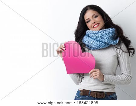 Smiling young woman in warm clothes with Valentine day pink paper heart card in her hands