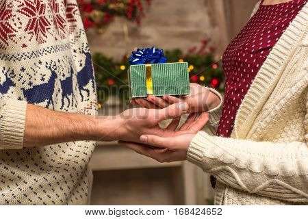 Partial view of young couple holding christmas present