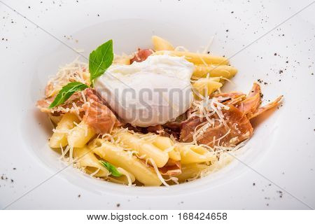 Pasta with bacon and poach egg on top. Selective focus on poach egg.