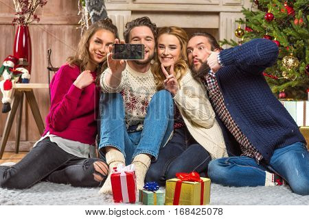 Happy young people taking selfie at christmastime