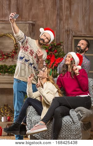 Group of happy young people having fun and taking selfie at christmastime