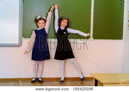Educational concept. Two happy schoolgirls standing together by a schoolboard in a classroom.