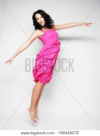 Jumping woman. Happy emotional girl. Long hair in motion.Studio shot.