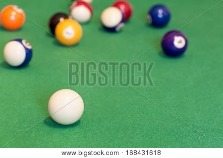 Pool balls and cue ball on green baize table