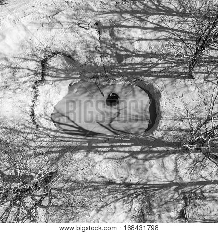 Black white photo of wellspring in the woods. Aerial view.