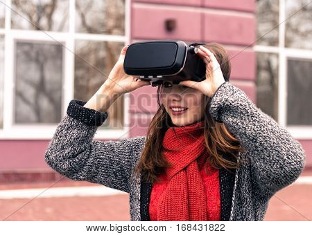 virtual reality headset VR glasses VR goggles - beautiful young girl with virtual reality headset or 3d glasses smiling on the street interested by 360 image