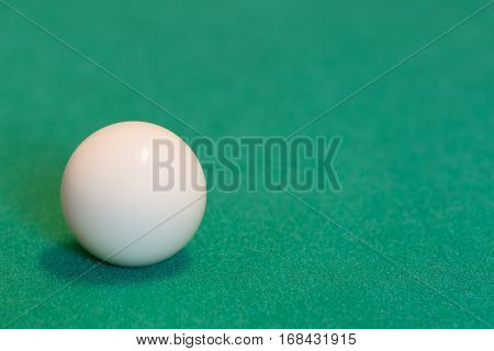 Pool cue ball on green baize table