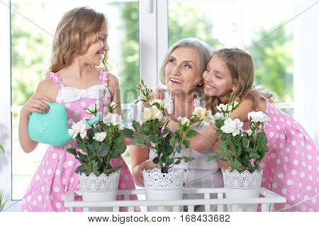 Portrait of a granny with her granddaughters watering flowers