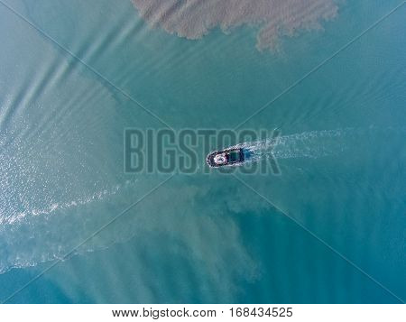 Aerial top view of motion tugboat at azure water with a spot of oil.