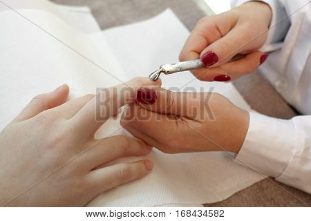 Manicurist removing cuticle from the girl client nail at beauty salon.